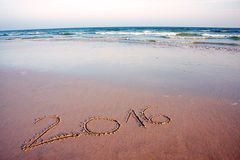 2016 written in sand on tropical beach, in sunset stock photo