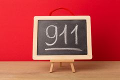 911 written on school blackboard. Against red background. Emergency concept, copy space Royalty Free Stock Photos