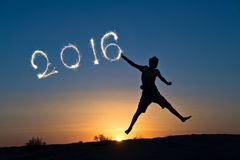 2016 written with sparkles, silhouette of a boy jumping Stock Image