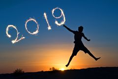 2019 written with sparkles, silhouette of a boy jumping in the sun. New year card stock photo