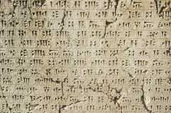 Written in stone. Ancient cuneiform writing carved into a stone wall creating a textured background Stock Photography