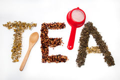 Written tea word with camomile, dog rose and green tea herbs Royalty Free Stock Photo
