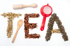 Written tea word with camomile, dog rose and green tea herbs Stock Image