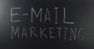 Written with a text: E-mail marketing on blackboard. royalty free stock images
