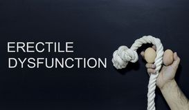 Written text: erectile dysfunction Man holding rope and two eggs as symbol of male penis Royalty Free Stock Image