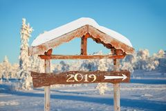 2019 written on a wood direction sign, blue sky and snowy landscape background. 2019 written on a wooden direction sign, blue sky and snowy landscape background royalty free stock photography
