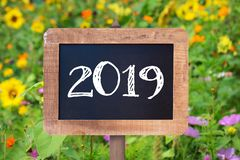 2019 written on a wooden sign, Sunflowers and wild flowers. In the background stock photo