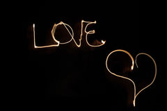Written word of love in the air in the darkness with fire Stock Photo