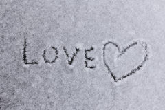 Written word love and a heart symbol on a white snowy background Stock Photography