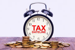 Written word Tax Dateline on a clock with gold coins on top of a. Wooden table. Financial Wealth Concept Stock Image