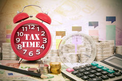 Written word Tax Time on a clock with compass ,coins and Calcula Royalty Free Stock Image