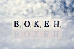 Written word of tiles with letters - bokeh Stock Images
