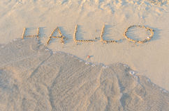 Written words Hallo on sand of beach Royalty Free Stock Images