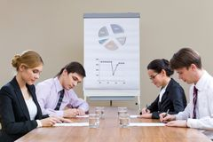 Written work. Two rows of businesspeople having written work at briefing royalty free stock images