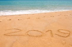 Written year 2019 on sand beach at the sea. royalty free stock photos