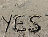 Written YES engraved on the sand of the Sea Beach Stock Photography