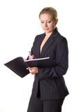 Writting dowm notes. Business woman writting down notes in her notepad Stock Image
