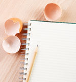 Writting a recipe. Directly above close-up view of a table with a Egg shells and a notebook Stock Photo