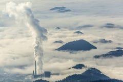 Wärmekraftwerk in der nebeligen Landschaft Stockbild