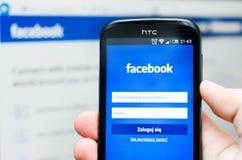 WROCŁAWSKI, POLSKA, WRZESIEŃ - 10, 2014: Wręcza mienia smartphone z Facebook sieci ogólnospołeczną wiszącą ozdobą app Obraz Royalty Free