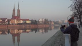 Young person takes picture of Cathedral Island in Wroclaw stock footage