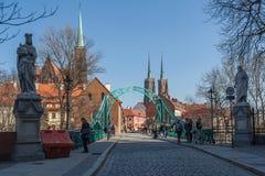 Wroclaw, Polônia - cerca do março de 2012: A maioria ponte, esculturas e de torres de Tumski da catedral gótico de St John o bati Fotografia de Stock Royalty Free