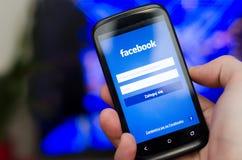 WROCLAW, POLÔNIA - 5 DE ABRIL DE 2014: Entregue guardar o smartphone com rede social app móvel de Facebook Fotografia de Stock Royalty Free