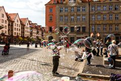 Man launches soap bubbles entertain tourists in the old city cen. WROCLAW, POLAND - APR 14, 2018: A man launches soap bubbles entertain tourists in the old city royalty free stock images