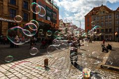 Man launches soap bubbles entertain tourists in the old city cen. WROCLAW, POLAND - APR 14, 2018: A man launches soap bubbles entertain tourists in the old city stock photo