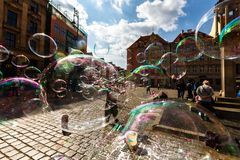 Man launches soap bubbles entertain tourists in the old city cen. WROCLAW, POLAND - APR 14, 2018: A man launches soap bubbles entertain tourists in the old city stock image