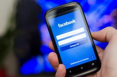 WROCLAW, POLAND - APRIL 05, 2014: Hand holding smartphone with Facebook social network mobile app Royalty Free Stock Photography