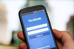 WROCLAW, POLAND - APRIL 05, 2014: Hand holding smartphone with Facebook social network mobile app Royalty Free Stock Photo