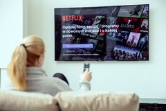 Woman is using NEtflix application on her TV. WROCLAW, POLAND - APRIL 03rd, 2018: Netflix is an american entertainment company specialized in streaming media royalty free stock photo