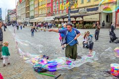– street entertainer – playing with children, making soap bubbles. Wroclaw/Poland- August 19, 2017: young man – street entertainer – playing with Royalty Free Stock Images