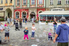 Street entertainer – playing with children, making soap bubbles. Wroclaw/Poland- August 19, 2017: young man – street entertainer – playing with children Royalty Free Stock Photos