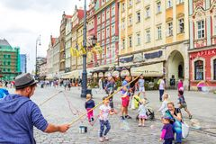 Street entertainer – playing with children, making soap bubbles. Wroclaw/Poland- August 19, 2017: young man – street entertainer – playing with children Royalty Free Stock Images