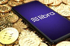 WROCLAW, POLAND - JUNE 20th, 2019: Facebook announces Libra cryptocurrency. Smartphone withLibra logo on the screen is laying down. On Libra concept coins stock image