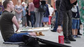 Artist crippled men draws paintings and good people throw money into tin on open air. Wroclaw, Poland 12 May 2018: artist crippled men draws paintings and good stock footage