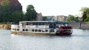 Excursion on water, motor ship with tourists is swim to pond past city houses behind trees in spring. Wroclaw, Poland 12 May 2018: excursion on water, motor ship stock footage