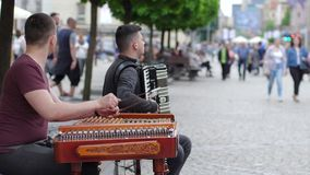 Street art, young people play musical instruments for passers by people at town in slow motion. Wroclaw, Poland 12 May 2018: street art, young people play stock video footage