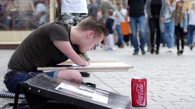 Street artist invalid, guy with disability draws paintings on street in city. Wroclaw, Poland 12 May 2018: street artist invalid, guy with disability draws stock video footage