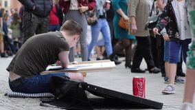 Street creativity, invalid guy makes paintings and compassionate people give money into jar at city area. Wroclaw, Poland 12 May 2018: street creativity, invalid stock video footage