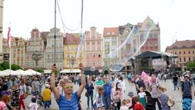 Street entertainment, men is making big soap bubble on air outdoors for people in city on weekends. Wroclaw, Poland 12 May 2018: street entertainment, men is stock video