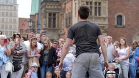 Street hobby, guy with ball makes performance into middle of crowd at city in slow motion. Wroclaw, Poland 12 May 2018: street hobby, guy with ball makes stock video