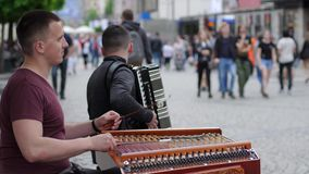 Street musicians play on xylophone and accordion for passersby at city in slow motion. Wroclaw, Poland 12 May 2018: Street musicians play on xylophone and stock video