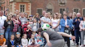 Street talent, guy does stunt with ball into front of crowd of people at town space in slow motion. Wroclaw, Poland 12 May 2018: street talent, guy does stunt stock video