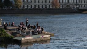 Group of young people, boys and girls, sit on riverbank in the city, have fun, pleasure activity, resting.
