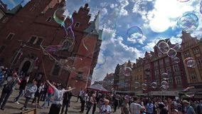 A man launches big soap bubbles entertain tourists in the old city center. Wide angle, slow motion. WROCLAW, POLAND - SEPTEMBER, 2018: A man launches big soap stock video footage