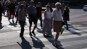 Silhouettes of people cross the street at a pedestrian crossing in the center of the city at rus