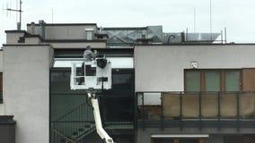 Wroclaw, Polen - April 25 2019: De arbeider wast de vensters buiten de woningbouw die zich op de cabine van de liftkraan bevinden stock video